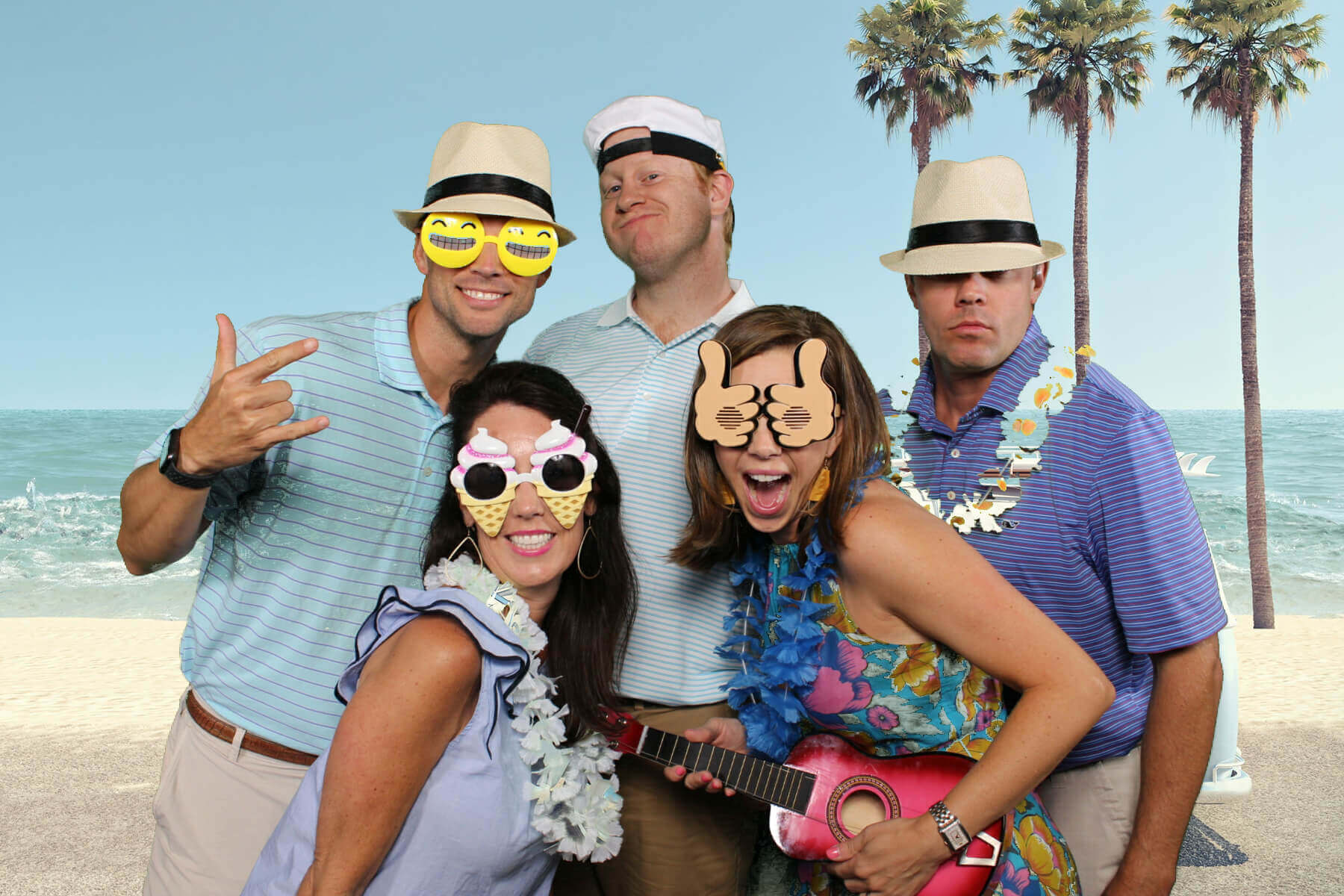 men with hats and women with fun sunglasses pose for photo booth in front of beach background