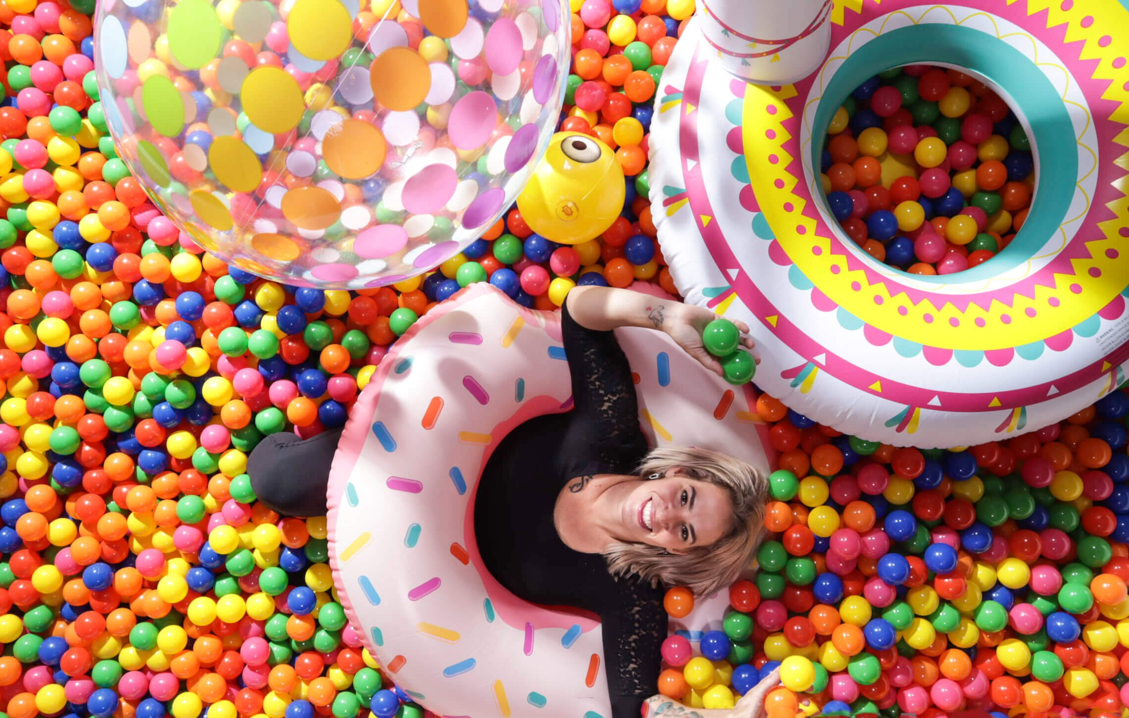 Woman in pink floatie inside a ball pit smiles to camera above